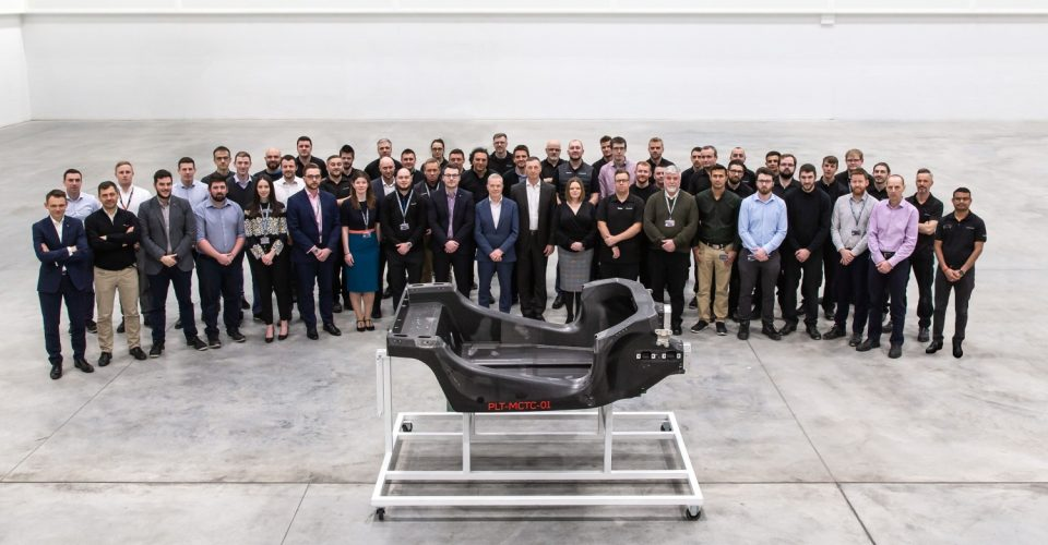 Mclaren staff posing for picture behind new carbon fibre body