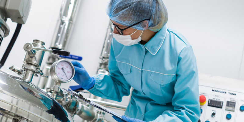 Man stood in PPE Equipment next to machine
